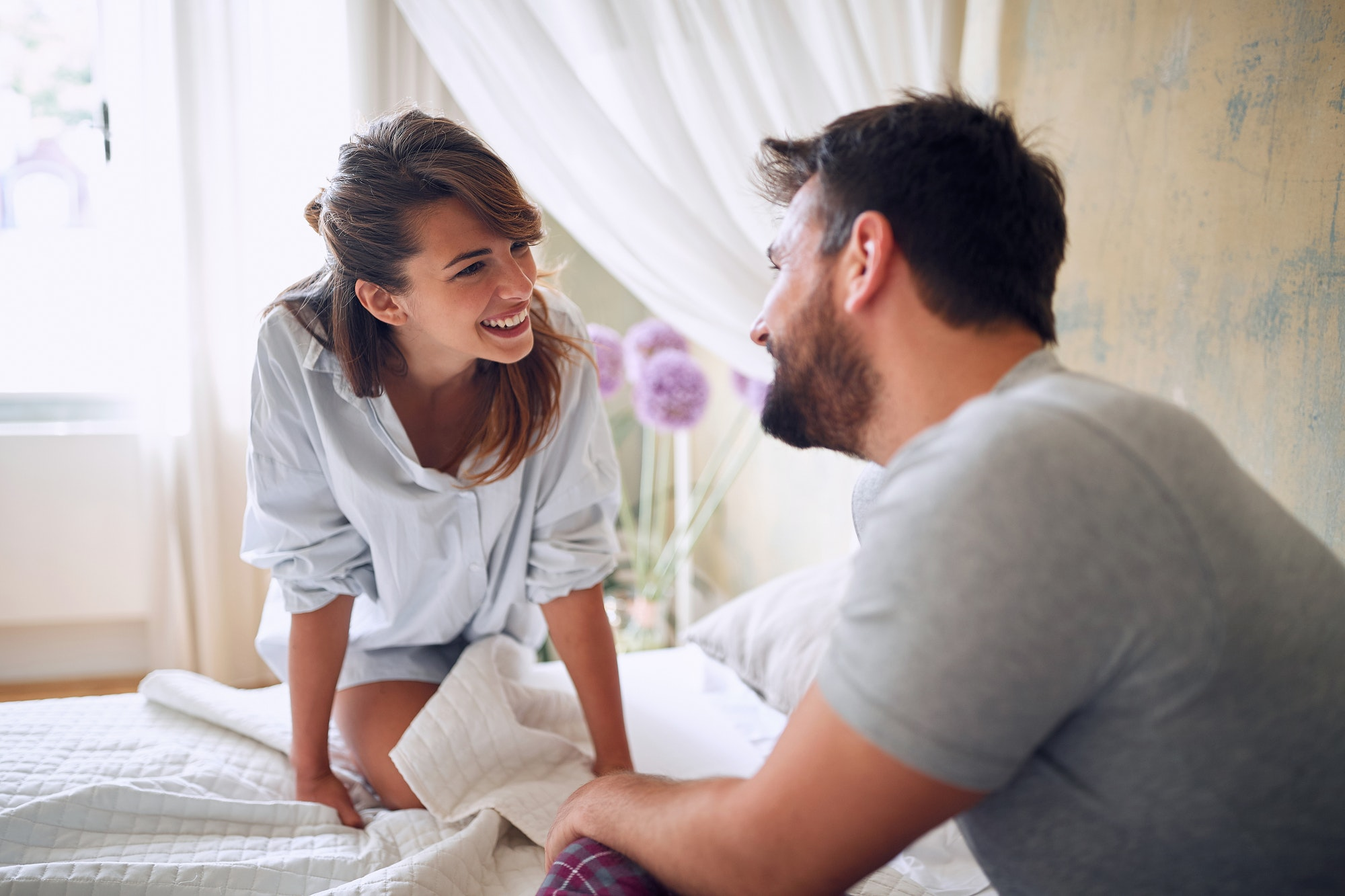 Smiling woman in bed showing emotions and love.Romantic couple in love on bed.